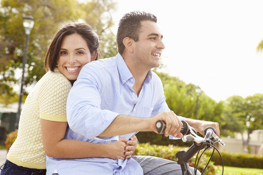 Young Hispanic Couple Riding Bikes In Park