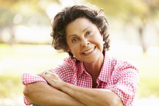 Portrait Of Senior Hispanic Woman Sitting In Park