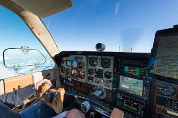 cockpit of old propeller airplane with tablet for navigation