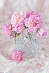 Beautiful fresh pink roses on a table .light background.