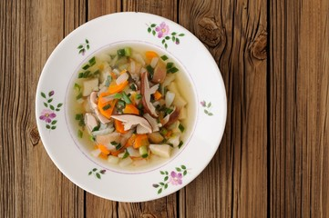 Porcini mushrooms soup in white plate on wooden background  copy