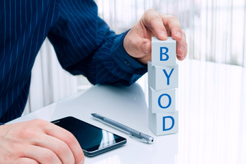 "Businessman arranging small blocks with word ""BYOD"""