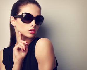 Elegant young female model in trendy sunglasses posing. Vintage