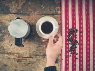 Coffee concept with cup and persons hand