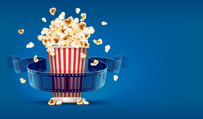Popcorn for cinema and movie film tape on blue background.