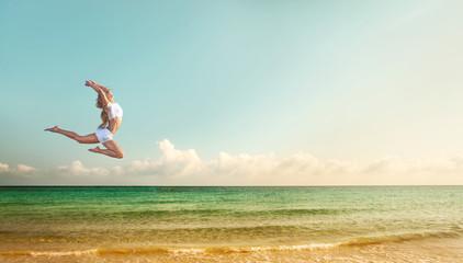 Beautiful fit woman  jumping at the beach near ocean