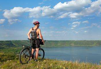 Mountain biker beside a beautiful Reservoir Bakota. Ukraine