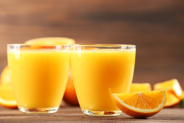 Orange juice on table on wooden background