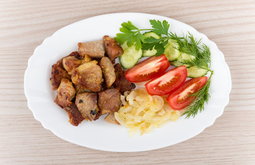 Fried pork and onions with tomatoes, cucumbers in dish