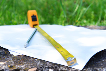 Building roulette and pencil on white sheets of paper, outdoors