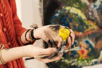 Brushes and oil paints in woman hands