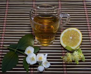 glass of tea from a linden with a lemon on a rug
