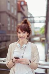 lächelnde junge frau mit kopfhörern und smartphone in der stadt