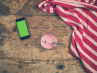 Yogurt and smart phone on table with tea towel