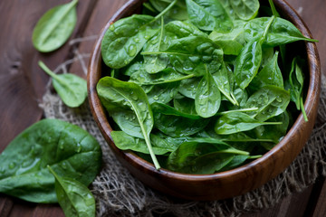 Wooden bowl with fresh spinach leaves, close-up, high angle view