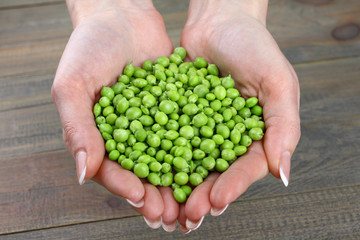 Woman holding fresh green peas