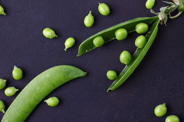 Fresh green peas on a black background