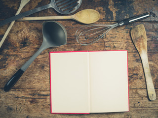 Kitchen utensils on wooden table with book