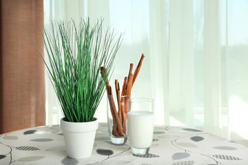 Green plant with glass of milk and cinnamon sticks on table on curtains background