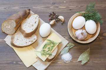 Bread, eggs, cheese, vegetables and spices on wood table