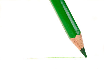 Sharpened green pencil draws a line on a white paper