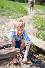 Little boy near clear mountain stream