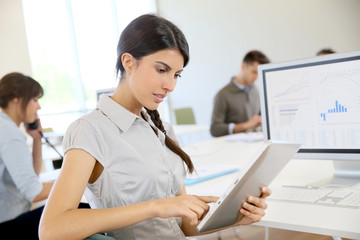 Young business girl working on digital tablet in office
