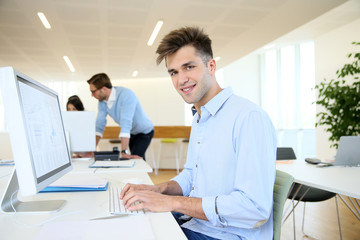 Office worker sitting in front of desktop, colleagues in background