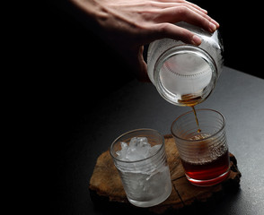 Fototapeta Man`s hand pouring hot and cold coffee into two glasses. Dark ba obraz