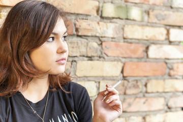 Schoolgirl teenager smokes outdoor on brick wall background
