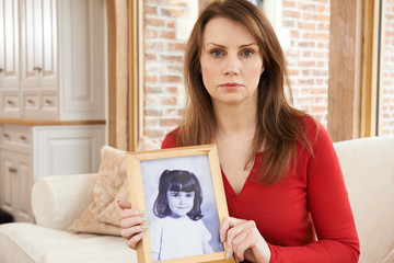 Unhappy Mature Woman With Photograph Of Daughter In Frame