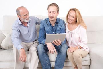 Eltern schauen mit Sohn auf ipad
