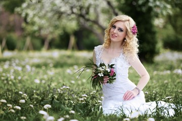 Beautiful young bride in white dress sits field in summer green park