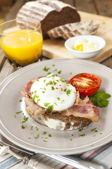 Poached egg and bacon on rye bread, healthy breakfast