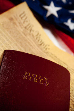 Constitution: Focus on Bible with Document and Flag Behind
