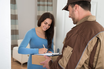 Young Woman Signing While Receiving Courier