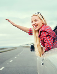 Happy smiling young woman in car window