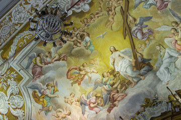 A colorful Italian Renaissance fresco on the arched ceiling of an ancient church.