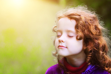 Little girl closed her eyes and breathes the fresh air in the pa