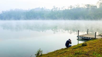 Photographer take a photo beside the lake at sunrise
