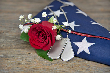 dog tags and red rose on folded American flag