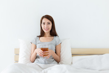 Asian woman holding a cup of tea and sitting on bed