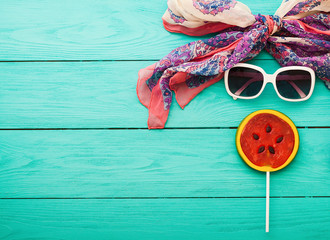 Candy and summer accessories on blue wooden background