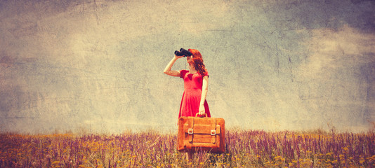 girl in red dress with suitcase and binocular