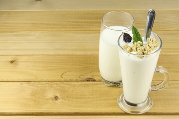 Glass of milk and yoghurt and muesli.