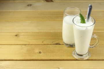 Glass of milk and yoghurt  stands on a wooden table. Healthy dietary breakfast.