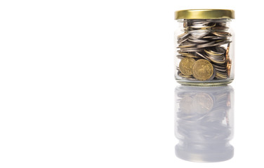 Malaysian coins in a mason jar over white background