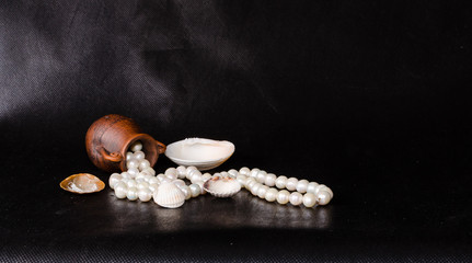 Ancient amphora, tropical sea shell and pearls over black