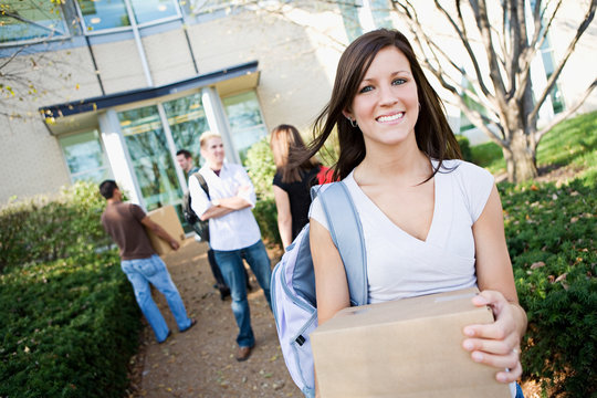 College: Girl Moving Into Dorm with Box