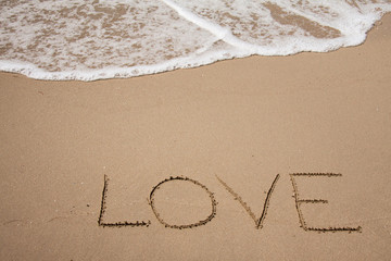 Love written on sand beach